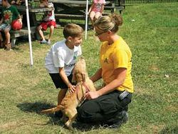 Kelly Schubert Demonstrating Animal Care with a young boy and a puppy